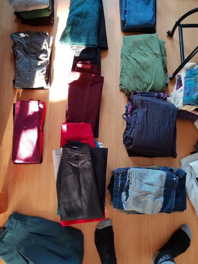 Mehrere Stapel ordentlich gefaltete Kleidung von oben fotografiert.
