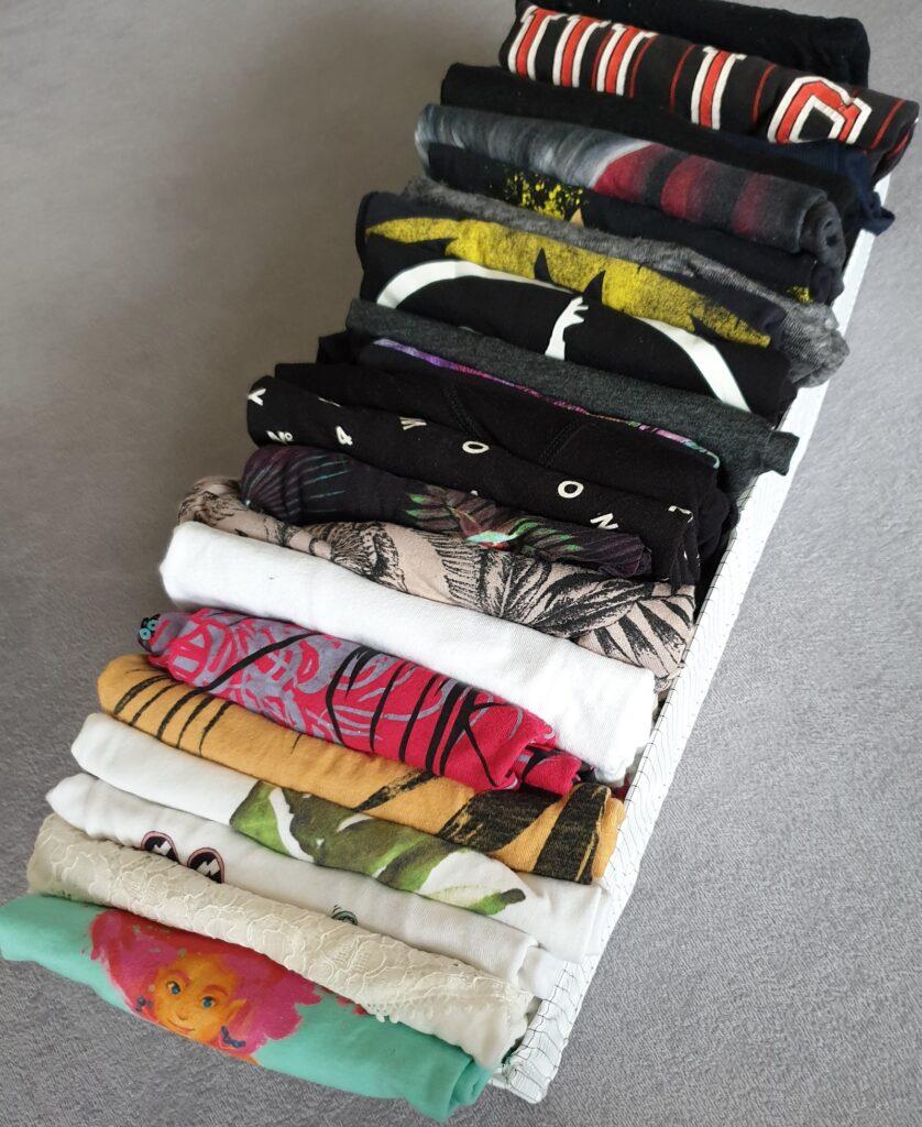 Eine Kiste mit fein säuberlich gefalteten, aufrecht stehenden T-Shirts