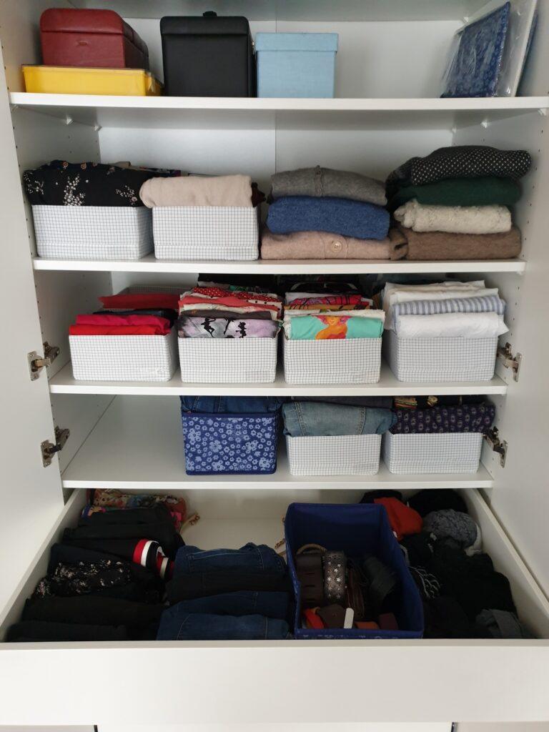 Ein Kleiderschrank mit einigen Kistchen, in denen aufrecht Kleidungsstücke stehen. Er sieht aufgeräumt aus.