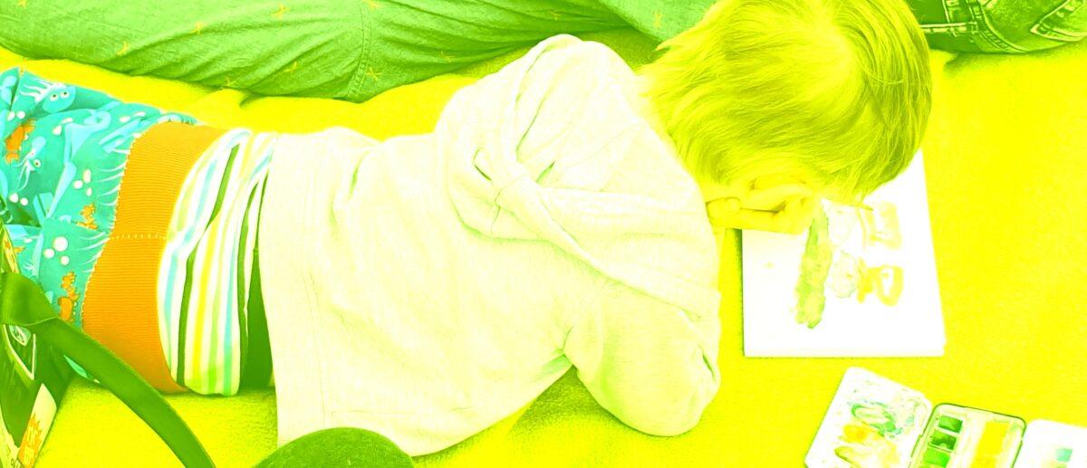 Ein Kind liegt auf dem Bauch und malt.
